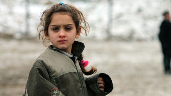 A Syrian girl plays in the snow in the Syrian city of Aleppo, which was bombed two days after this photo was taken on December 13.