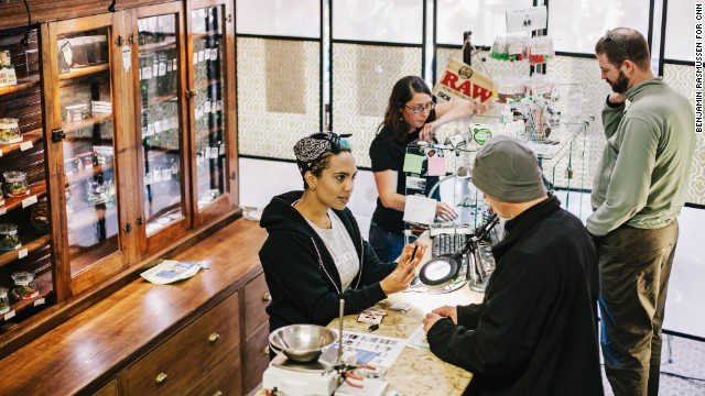 Beej Jackson (left) and Amber Bacca serve customers in Evergreen Apothecary in Denver, CO. The first legal recreational marijuana sales took place at 8:00 this morning.