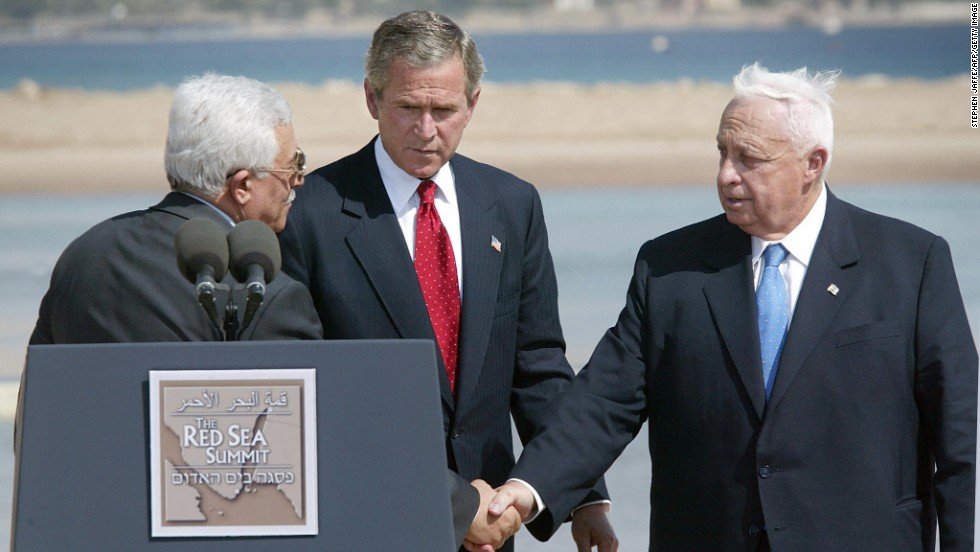 "In June 2003, Sharon, right, met with Palestinian Authority leader Mahmoud Abbas, left, and U.S. President George W. Bush to discuss a Middle East ""road map"" for peace. After the meeting, Sharon expressed his ""strong support"" for a two-state solution to the Israeli-Palestinian conflict."