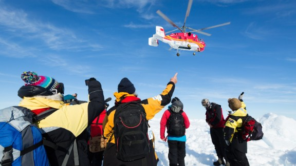 This image taken by expedition doctor Andrew Peacock of www.footloosefotography.com on January 2, 2014 shows a helicopter from the nearby Chinese icebreaker Xue Long above passengers from the stranded Russian ship MV Akademik Shokalskiy as the first helicopter rescue takes place after over a week of being trapped in the ice off Antarctica. The helicopter mission to rescue 52 passengers trapped on the icebound Russian research ship finally got underway in Antarctica on January 2 after a number of false starts and failed icebreaking attempts. It was expected to take at least five hours to ferry all passengers from the icebound vessel to the Xue Long -- 10 nautical miles distant -- by helicopter, with five flights of up to 12 passengers and a return journey taking 45 minutes. The ship is carrying scientists and tourists who are following the Antarctic path of explorer Douglas Mawson a century ago, details of which at www.spiritofmawson.com, and have been carrying out the same scientific experiments his team conducted during the 1911-1914 Australian Antarctic Expedition -- the first large-scale Australian-led scientific expedition to the frozen continent. RESTRICTED TO EDITORIAL USE AFP PHOTO / MANDATORY CREDIT: Andrew Peacock / www.footloosefotography.comAndrew Peacock/AFP/Getty Images