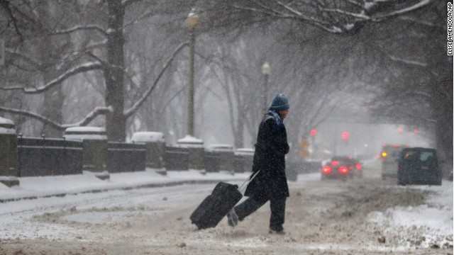 A man drags a suitcase on a snowy street in downtown Boston, on Thursday, January 2. Up to 14 inches of snow is forecast for the Boston area.
