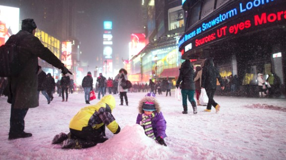 Children make a snow pile in New York