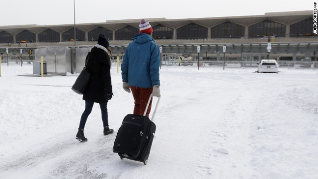 Travelers walk across a snow-covered parking lot at Newark Liberty International Airport on Friday.