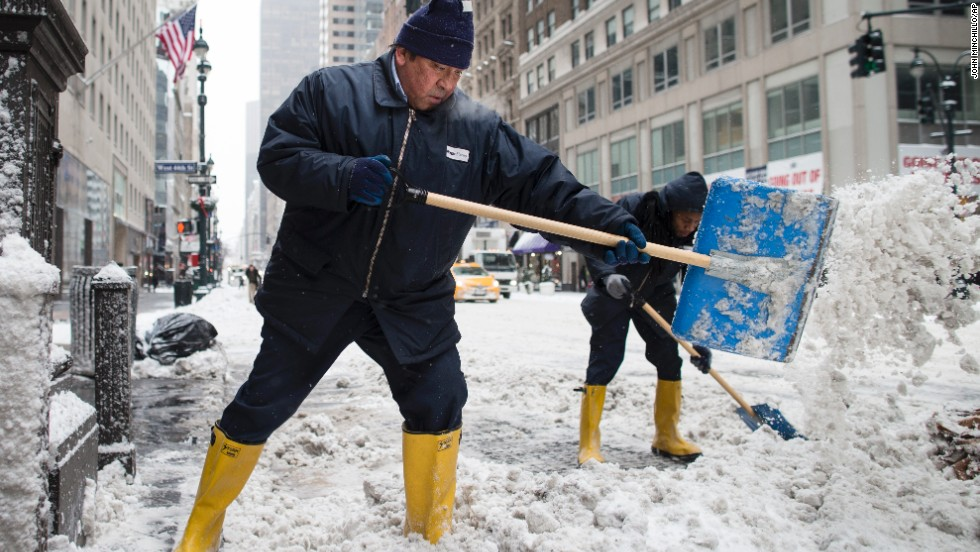 Workers clear snow off sidewalks on New York City's Fifth Avenue on January 3.