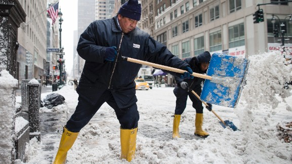 Workers clear snow off sidewalks on New York City