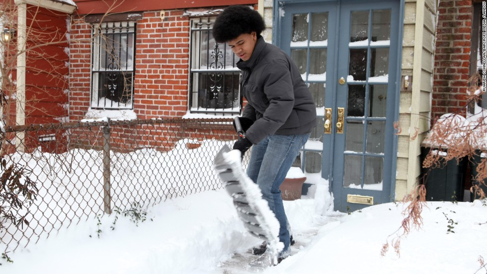 Dante de Blasio, son of New York Mayor Bill de Blasio, shovels snow outside his home in Brooklyn on January 3.