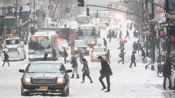 Pedestrians brave wind and snow as they cross New York City