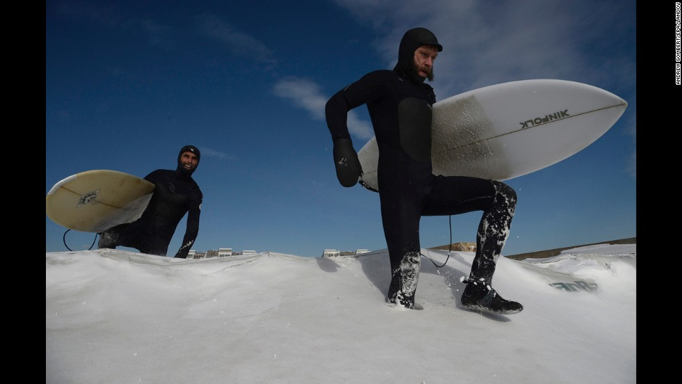 Surfers make their way through snow on New York's Rockaway Beach on January 3.