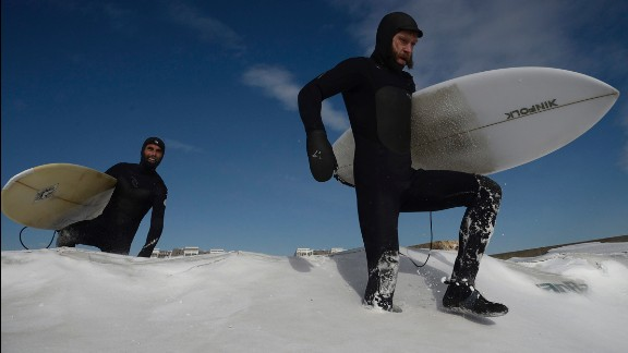 Surfers make their way through snow on New York