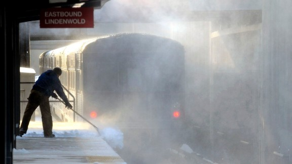 Blowing snow swirls as a worker shovels a platform at a Haddonfield, New Jersey, train station on January 3.