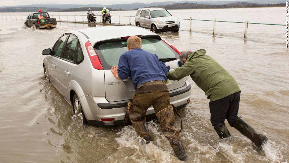 People push a car toward higher ground in Storth, England, on January 4.