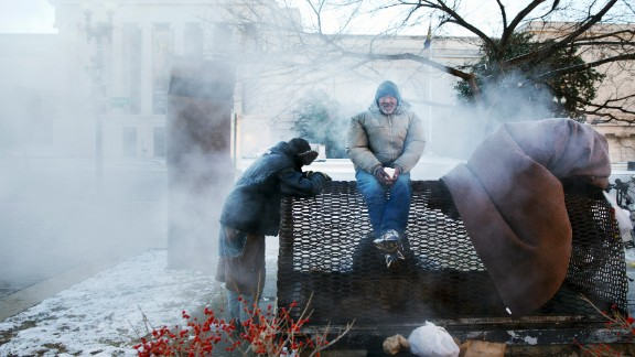 Four homeless men warm themselves on a steam grate by the Federal Trade Commission Building, blocks from the U.S. Capitol in Washington, as frigid temperatures grip the nation