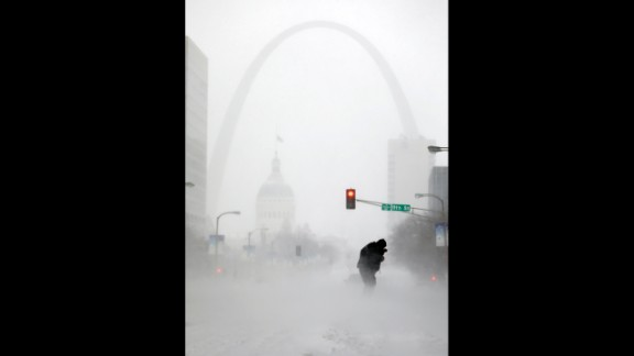 With the Gateway Arch in the distance, a person struggles to cross the street during a snowstorm January 5 in downtown St. Louis.
