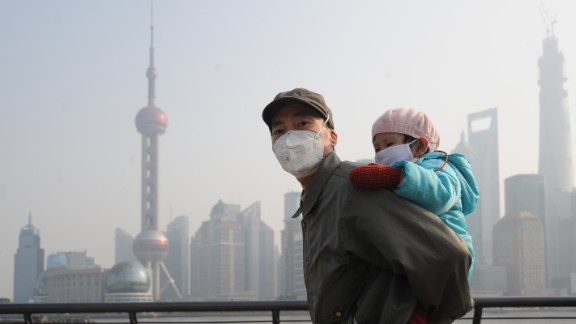 SHANGHAI, CHINA - DECEMBER 25: (CHINA OUT) A man and his child wear masks as they visit The Bund on December 25, 2013 in Shanghai, China. Heavy smog covered many parts of China on Christmas Eve, worsening air pollution. (Photo by ChinaFotoPress/ChinaFotoPress via Getty Ima