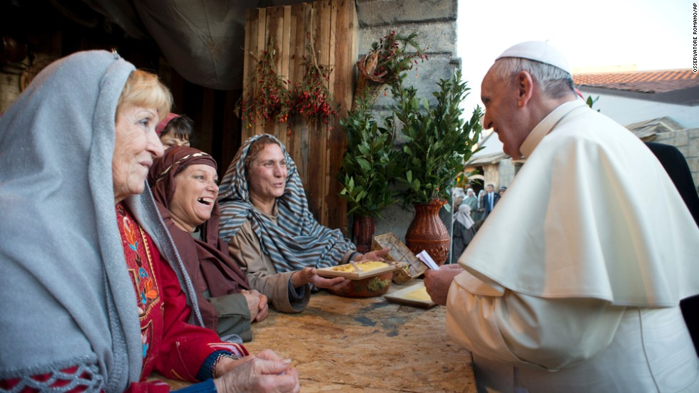 The Pope greets a group of women participating in the nativity scene.