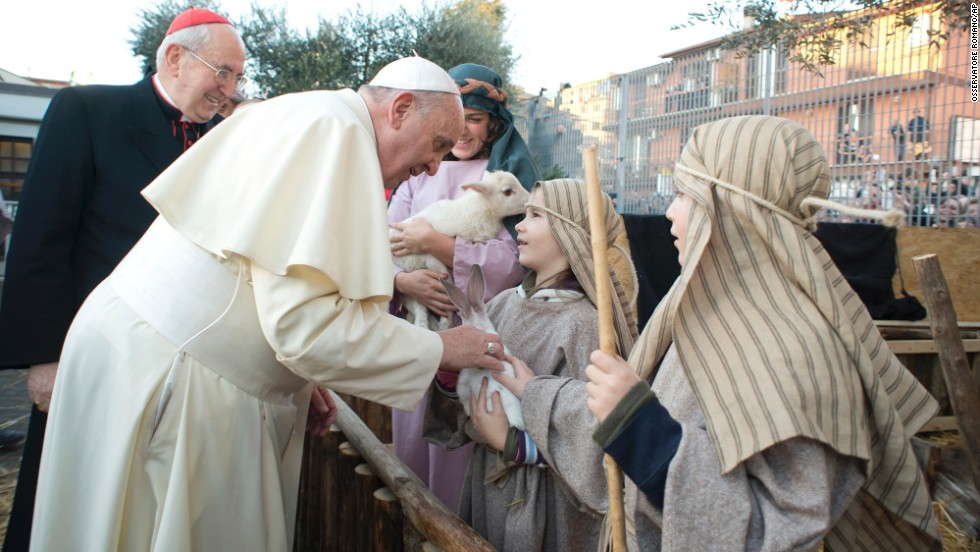 The Pope greets children participating in the nativity scene.