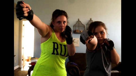 """Jenni Conner of Santa Maria, California, and her 9-year-old daughter, Skylar, do a combat fitness program together at home every night. """"I don't have to ask, she wants to do it,"""" said Conner, a mom of two. """"She has lost weight and built muscle. ... It's all because she watched her mom and chose to follow my lead."""""""