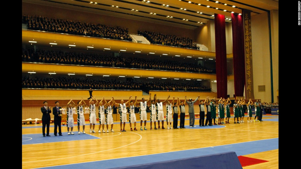 U.S. and North Korean basketball players raise their hands to the crowd after the game.