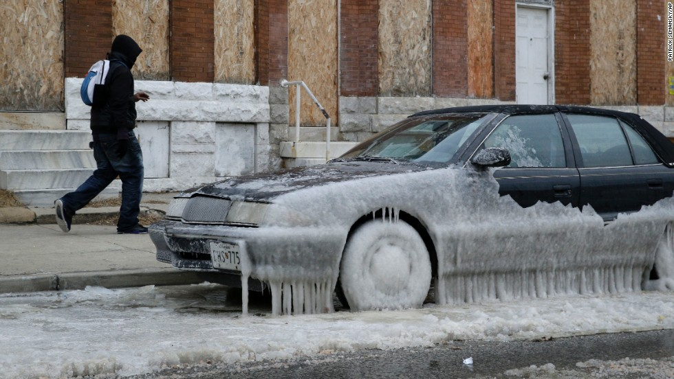 A man walks past a car in Baltimore that is partially covered in ice January 8.