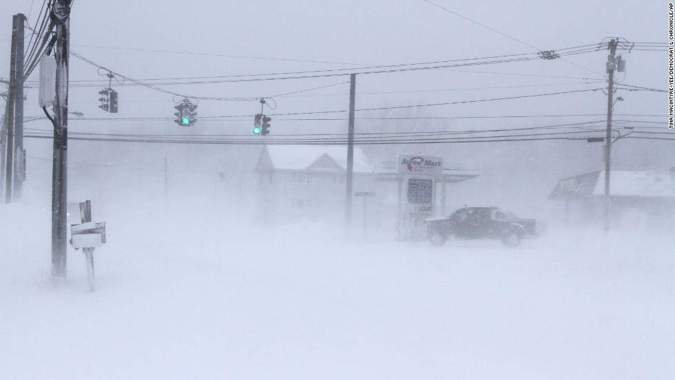 A vehicle drives through a barely visible intersection in Stafford, New York, on January 7.