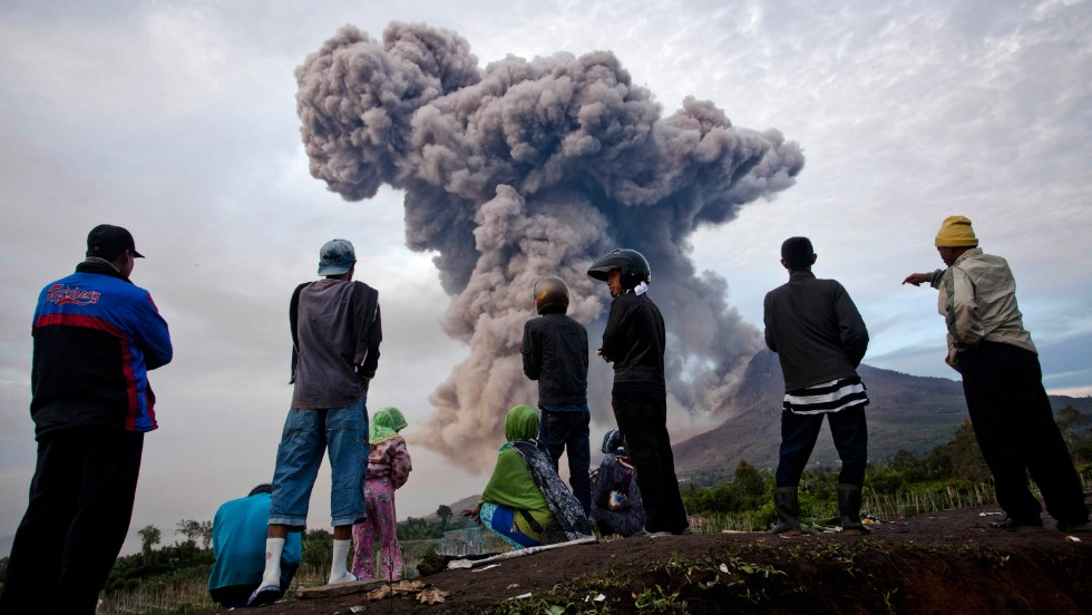 People watch as Mount Sinabung smokes.