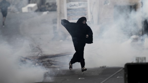 A protester runs from tear gas fired by Bahrain
