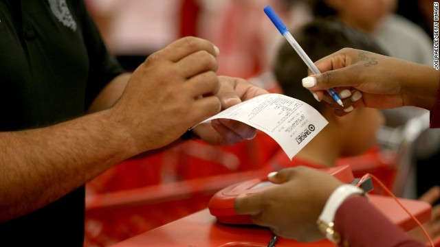 MIAMI, FL - DECEMBER 19: A customer prepares to sign a credit card slip at a Target store on December 19, 2013 in Miami, Florida. Target announced that about 40 million credit and debit card accounts of customers who made purchases by swiping their cards at terminals in its U.S. stores between November 27 and December 15 may have been stolen. (Photo by Joe Raedle/Getty Images)