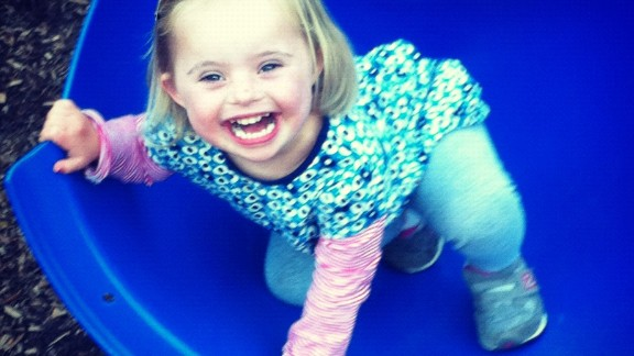 Ellie clambers off a playground slide at 4.