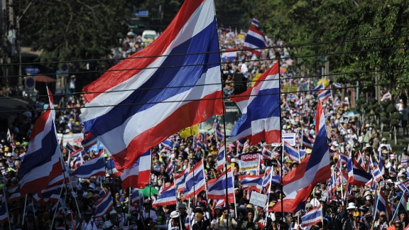 """Thai anti-government protesters wave national flags as they march through the streets of Bangkok in a move to """"shut down"""" the city on January 13, 2014."""