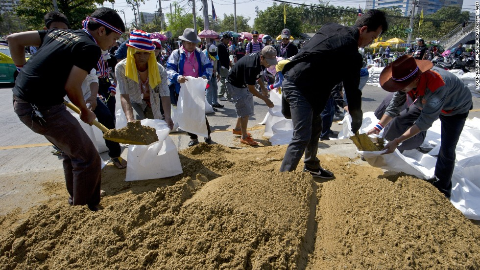 Anti-government protesters fill sandbags as they make barricades during a Bangkok rally on January 13, 2014.