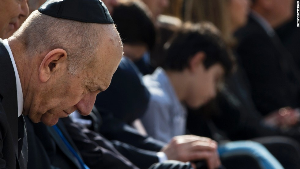 Former Israeli Prime Minister Ehud Olmert bows his head during the service.