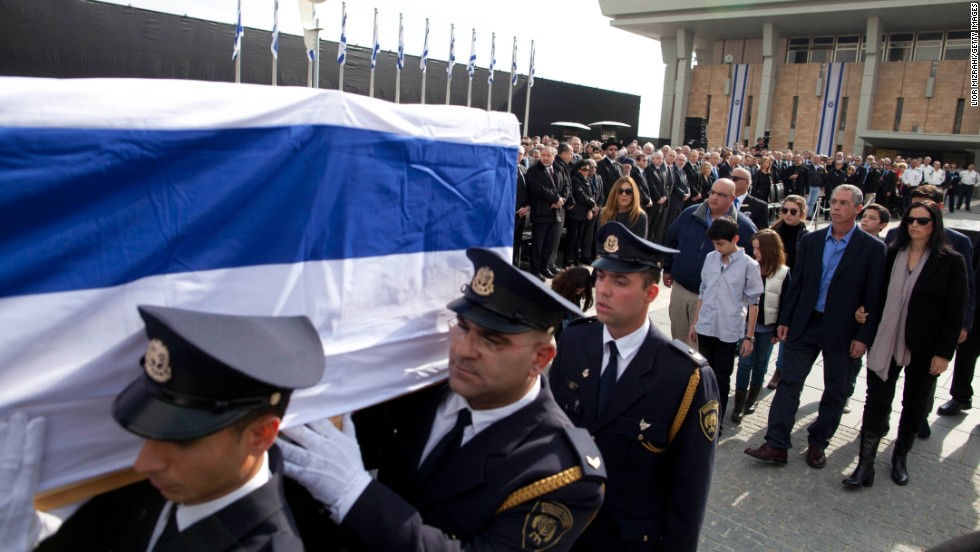 Members of the Sharon family follow the Israeli honor guard carrying the casket.