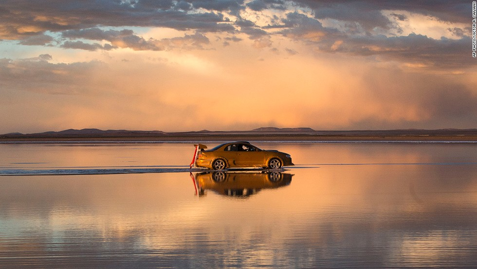 "JANUARY 13 - UYUNI, BOLIVIA: The sky is reflected on the Salar de Uyuni, the world's largest salt flat, as a car participates in the<a href=""http://cnn.com/2014/01/10/sport/motorsport/motorsport-dakar-rally-competitor-killed/""> Dakar Rally</a> on January 11. The dangerous marathon rally is an annual off-road race for motorcycles, ATVs, cars and trucks that takes place in South America, principally Argentina and Chile."