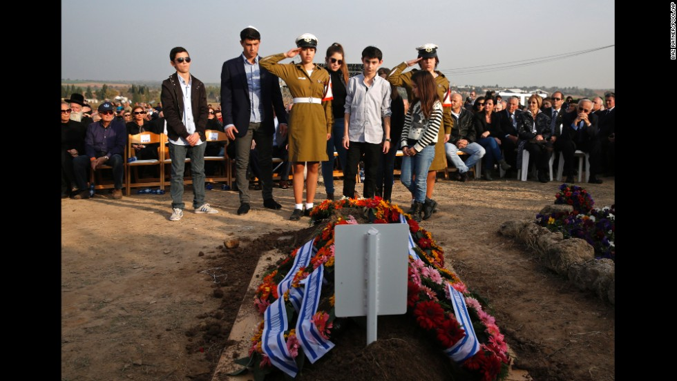 Sharon's grandchildren stand in front of his grave during his funeral near Sycamore Farm, Sharon's residence in southern Israel.