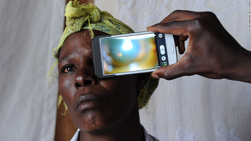 A technician scanning the eye of a woman with a smartphone application in rural Kenya.<br />