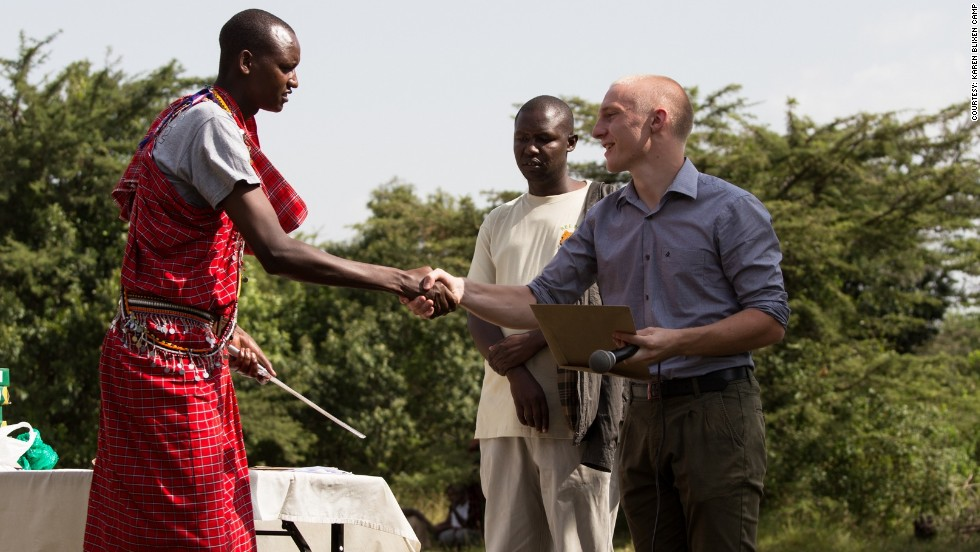 Eriksen presents one of his students, dressed in traditional Maasai clothing, with a diploma from the cooking school. He said many of the students go on to work in the local tourism community.