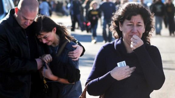 A woman waits at a staging ground area where families are being reunited with Berrendo Middle School students after a shooting at the school, Tuesday, Jan. 14, 2014, in Roswell, N.M. A shooter opened fire at the middle school, injuring at least two students before being taken into custody. Roswell police said the school was placed on lockdown, and the suspected shooter was arrested. (AP Photo/Roswell Daily Record, Mark Wilson)