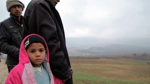 Syrian refugees newly arrived in Turkey look at the Syrian border from the Turkish side on January 14, 2014 in Kilis.