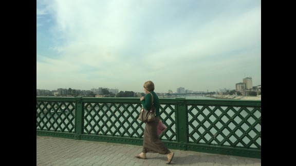 In this image taken on January 15, a woman walks through central Baghdad, Iraq, crossing a bridge over the Tigris River. CNN