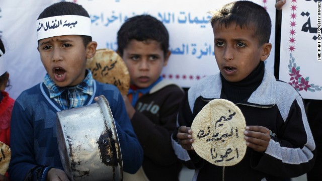 Palestinians children holds bread and pots on January 8, 2014, as they take part in a protest against the poor living conditions at the Yarmuk refugee camp in the Syrian capital Damascus, on January 8, 2014, in Rafah town in the southern Gaza Strip.