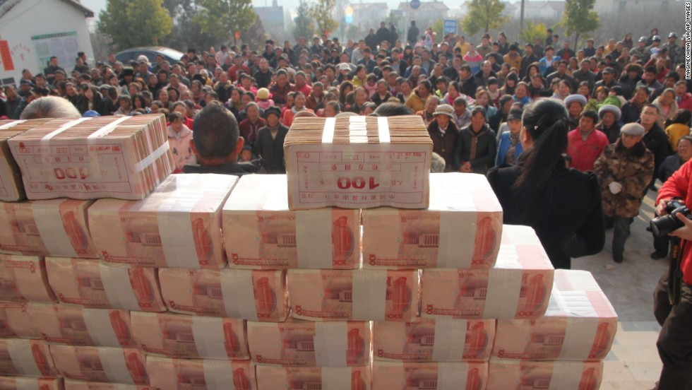 "Villagers stand in front of a ""money wall"" in Sichuan, China waiting to collect their year-end bonus from their investments in January 2014."