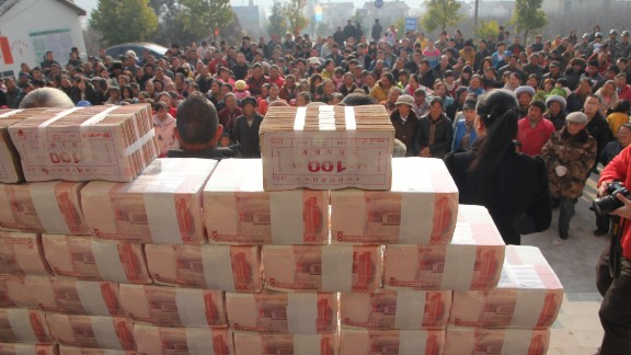 """Villagers stand in front of a """"money wall"""" in Sichuan, China waiting to collect their year-end bonus from their investments in January 2014."""