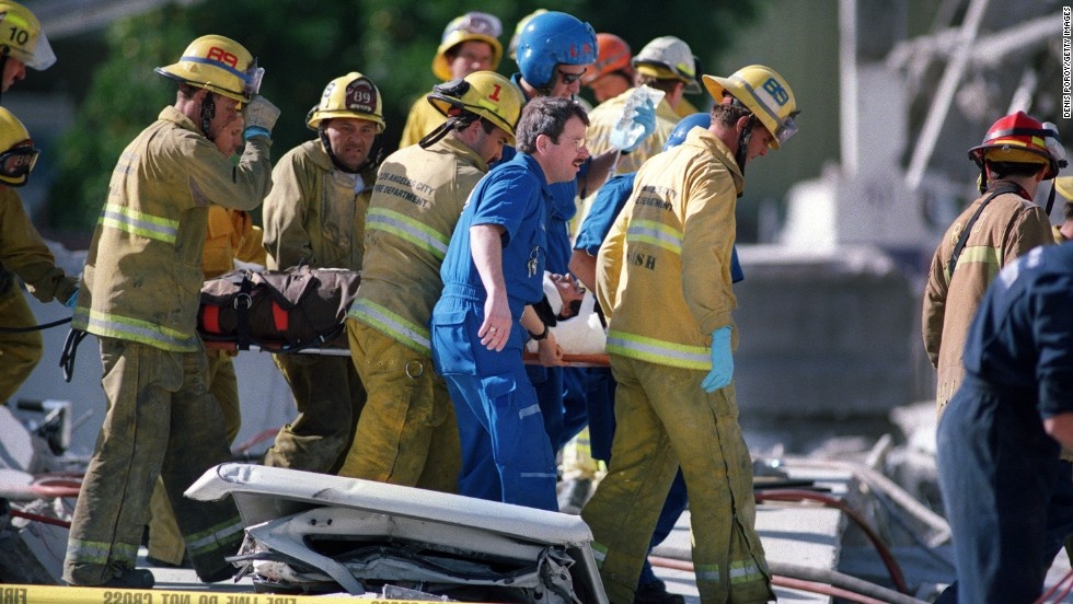 Firefighters carry a janitorial worker who was rescued from a collapsed garage at the Northridge Mall in Northridge, California. The earthquake occurred in the early morning, at 4:31 Pacific Standard Time.