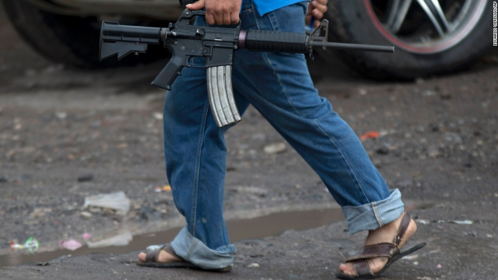 A member of a self-defense group carries a weapon in Antunez, Mexico, on Thursday, January 16. The western state of Michoacan has long been a flashpoint in Mexico's drug war, and such groups have said they were forced to protect violence-torn towns from cartels. The Mexican government has now stepped in, sending federal forces to the region and ordering the vigilante groups to lay down their arms.