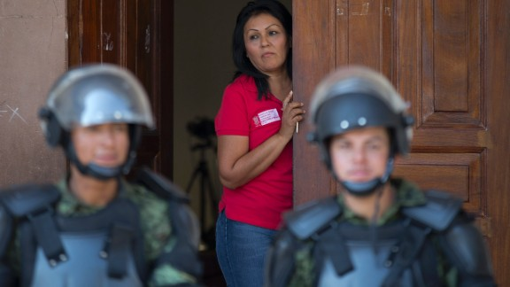 A city employee watches from a doorway as Mexican soldiers guard Apatzingan City Hall on January. 14. Mexican soldiers and federal police have faced tense standoffs with vigilantes after the government campaign to stop violence turned deadly.