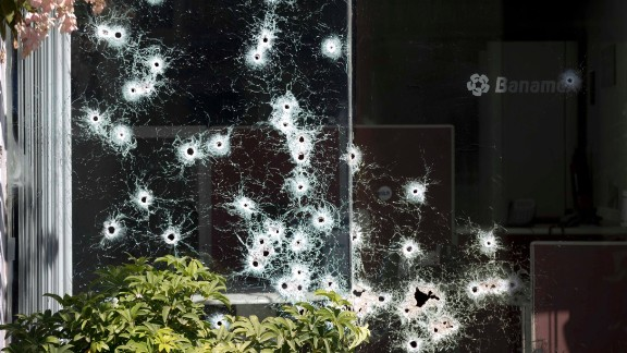 A bank window is riddled with bullet holes in Apatzingan on January 11. Some observers say it's not clear the Mexican government's crackdown is working.