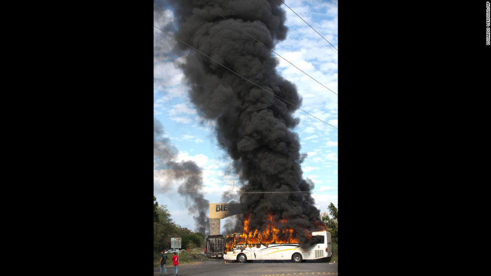 A bus burns at the entrance of Paracuaro on January 10. Some residents have responded to the vigilante groups' arrival by destroying property and setting vehicles ablaze to create road blocks to stop them.