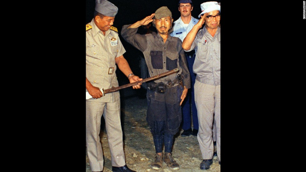 Hiroo Onoda, center, salutes after handing over his military sword on Lubang Island in the Philippines in March 1974. Onoda, a former intelligence officer in the Japanese army, had remained on the island for nearly 30 years, refusing to believe his country had surrendered in World War II. He died at a Tokyo hospital on Thursday, January 16. He was 91.