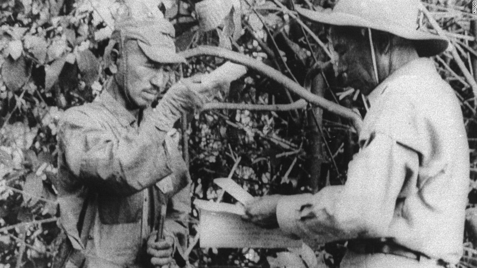 Onoda, left, accepts a pack of cigarettes from a member of a Japanese team sent in 1974 to persuade him the war had ended.
