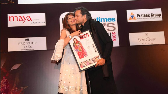 """Indian Human Resources Minister Shashi Tharoor kisses his wife, Sunanda Pushkar, at the """"Delhi's Most Stylish People's Choice Awards 2013"""" at the Oberoi Business Hotel on March 21, 2013, in Gurgaon, India. His wife was found dead in a luxury hotel after accusing him of being unfaithful. Her body was taken to the All India Institute of Medical Sciences for examination."""